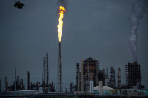 a gas flare and buildings of the Shell Petroleum plant in Norco, Louisiana, against a dark sky