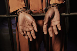 Black hands poke through orange sleeves, handcuffed around metal bars