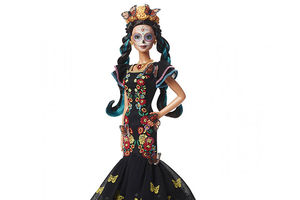 Dia de Muertos doll. Plastic doll with face painted like a white skeleton wears a crown of marigolds and a black dress with multicolored flowers and yellow butterflies.