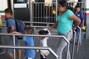 A woman wearing a blue shirt and gray jeans stands in line next to a silver barrier, along with her three small children.