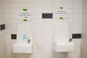 Two white water fountains on white tiled walls with signs warning people not to drink from them