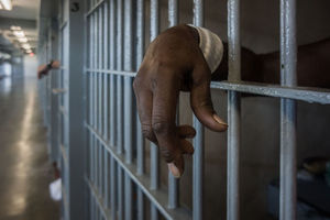 Black person's hand shown through prison cell bars.