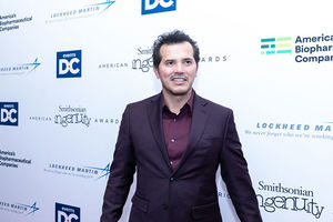 John Leguizamo. Latinx man with short dark hair wearing dark tuxedo jacket and purple shirt in front of step and repeat.
