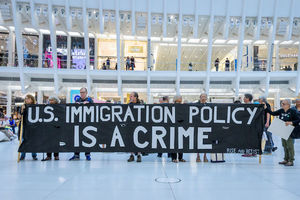 """A group of protestors hold a sign that reads, """"U.S. Immigration Policy is a Crime"""""""