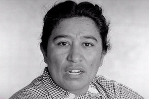 Maria Moreno. Black and white photo of Latinx woman with dark hair wearing checkered shirt.