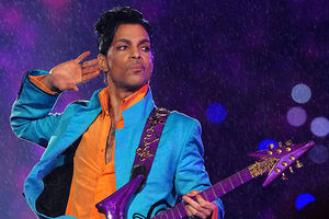 Prince. Black man with short dark hair wearing blue suit holding a guitar in the rain.