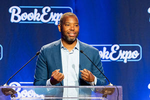 Ta-Nehisi Coates. Black man with short hair wearing a blue suit jacket and white shirt standing in front of podium.