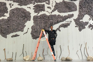 Wangechi Mutu. Black woman dressed in black standing on ladder in front of wall art.