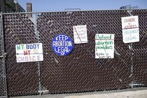 Signs in support of abortion rights hang on a metal fence