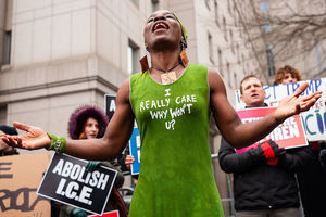 "Patricia Okoumou. Black woman wearing a green dress that reads, ""I really care, why won't u?"""