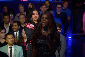 Blossom Brown. Black trans woman with long brown hair wearing dark colored dress holding a microphone.