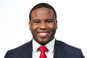 Botham Jean. Smiling Black man in dark suit jacket, white shirt and red tie