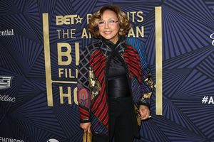 Diahann Carroll. Middle-age Black woman with shoulder length brown hair wearing geometric print top and glasses.
