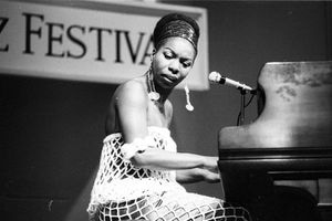 Nina Simone. Black and white photo of a Black woman in dress with large-gauge white netting sits at a piano.