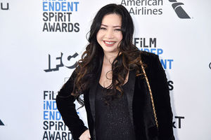 Nina Yang Bongiovi. Asian American woman with long dark hair wearing  black tuxedo jacket and black top.