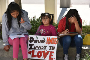 """Three young girls with dark hair sit on a curb holding a sign that reads, """"Defund hate, invest in love."""""""