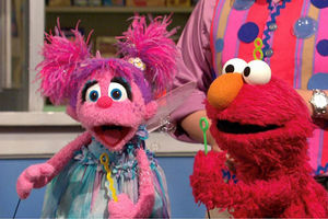 Two Sesame Street characters. Elmo is red and is blowing bubbles. Abby is pink and looks surprised.