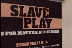 "A brown and peach sign has the words ""Slave Play"" and a recommendation of 17+"