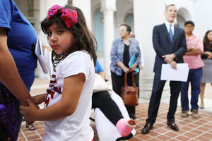 Young Latinx girl with dark hair and a pink bow in her hairs hold both hands of the woman next to her.