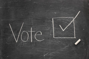 "White writing on black chalkboard reads ""vote"""