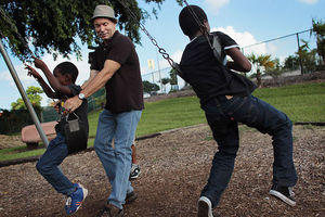 two boys playing on a swing with a man in a hat