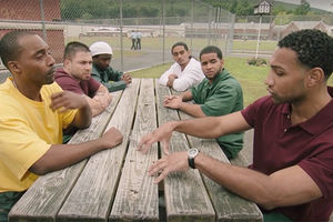 Six men wearing different colored shirts sitting at a long wooden table outside, talking.