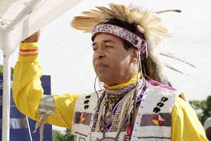 Lance Gumbs. Native American Shinnecock man dressed in traditional feathered headdress. with white beaded vest and yellow jacket.