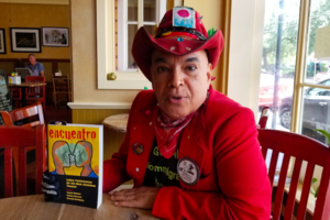 """A Equadorian man wears a red cowboy hat and matching suit and holds up a book titled """"Encuentro."""""""