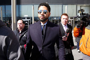 Jussie Smollet. Black man wearing dark suit with sunglasses surrounded by media.