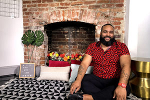 A Black man in a red printed shirt sits on a couch in front of an exposed brick wall and fireplace