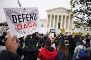 "Protester in front of the U.S. Supreme Court holds a sign that reads, ""Defend DACA."""