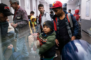 A small boy holds a dinosaur and stands next to his father, who wears a gray jacket. They are standing in a crowded bus station in Tucson, Arizona.