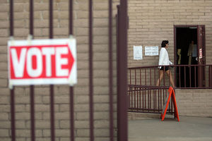 "A red and white ""vote"" sign is in the foreground, with a voter walking to the polls in the distance."