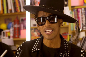 Raphael Saadiq. Black man wearing black fedora dressed in black studded jacket and black sunglasses.
