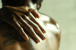 A Black person caresses their bare shoulder.