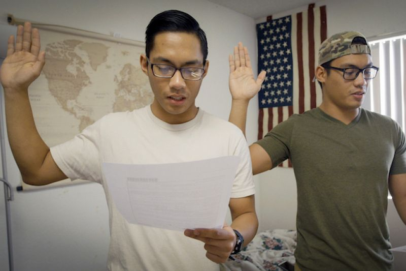 James and John Sena. Two Filipino men in white and green shirts holding right hands up in front of red and white and blue United States flag